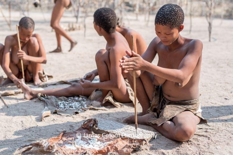 Woman form Bushmen tribe making jewellery, Namibia