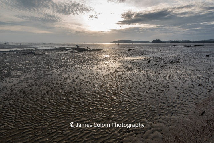 Walkers on Ao Nang Beach at sunset during low tide near Krabi, Thailand